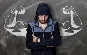 man with arms folded, but flexed muscles drawn on chalkboard behind him