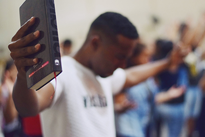 man holding Bible with outstretched hands and praying with