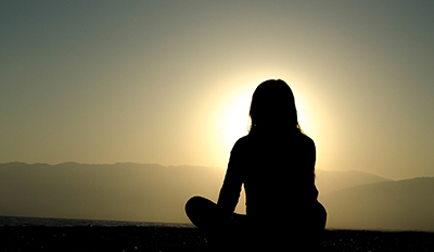silhouette of woman sitting cross-legged