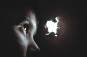 boy in darkness peering through an opening of light