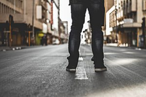 man's legs facing down a long street