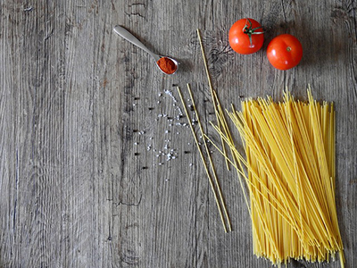 a handful of uncooked spaghetti and two small tomatoes on a table