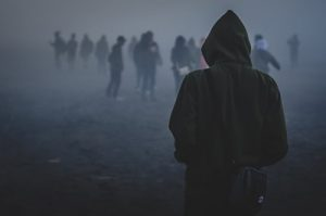 young man in hoodie facing a distant crowd through the fog