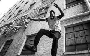 young man jumping off of a fire escape