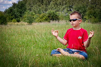 young boy in meditation pose