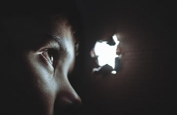 boy in darkness peering through an opening of light