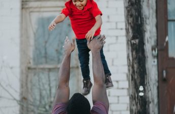 dad tossing boy in the air