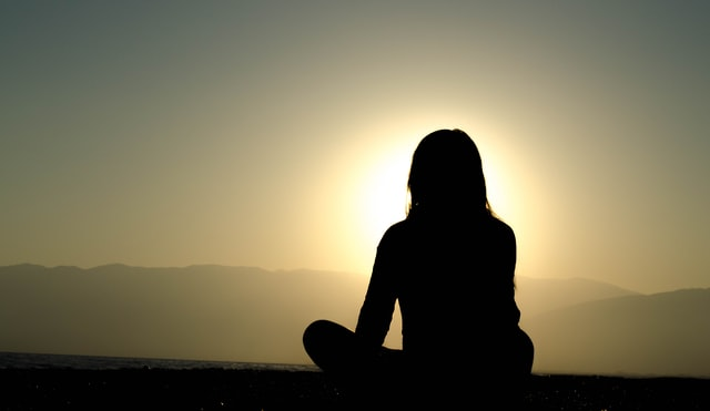 silhouette of teen in lotus position