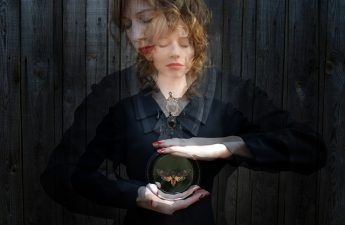 woman in black hoding crystal ball